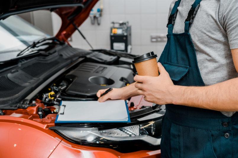 Homem jovem segurando uma prancheta e um copo de café em frente a um carro com o capô aberto, performando teste de bateria.