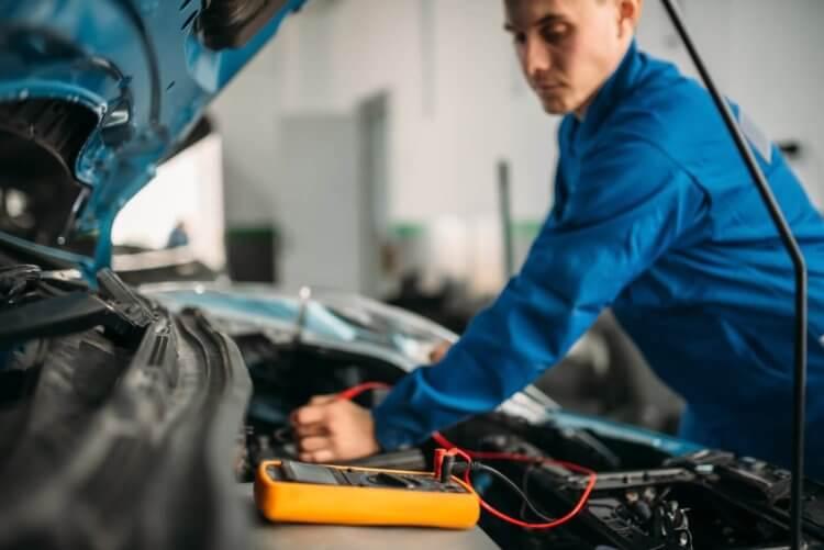 Imagem de mecânico arrumando uma bateria arriada
