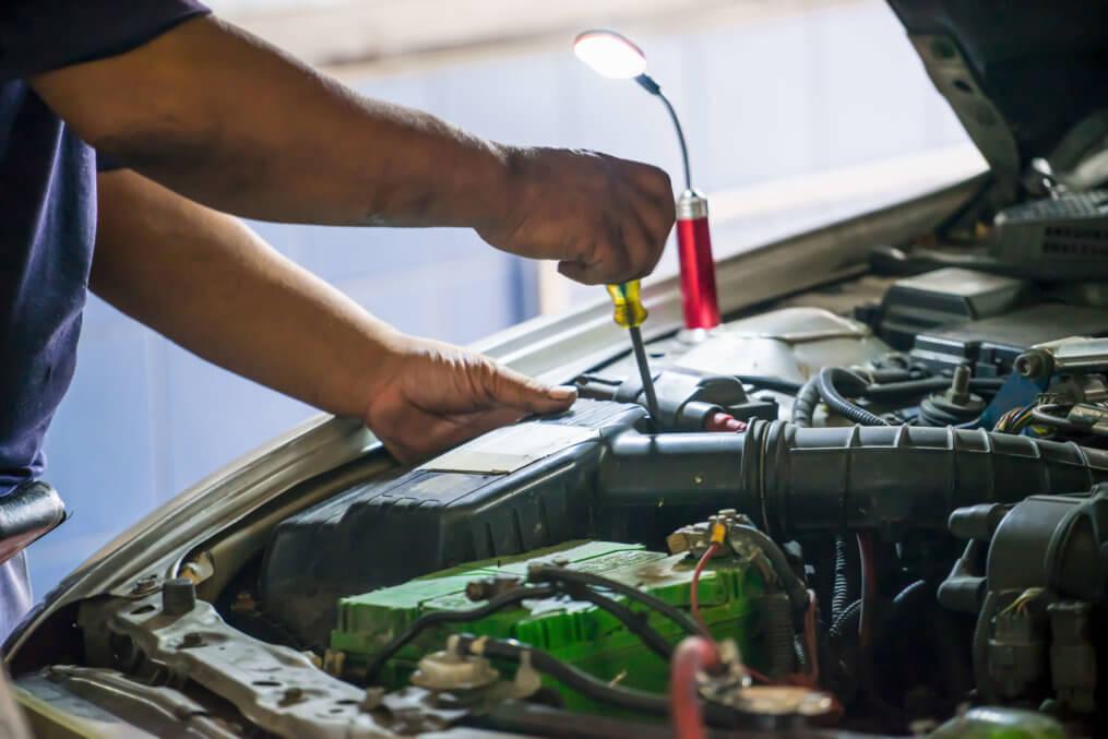homem mostrando como funciona uma bateria automotiva