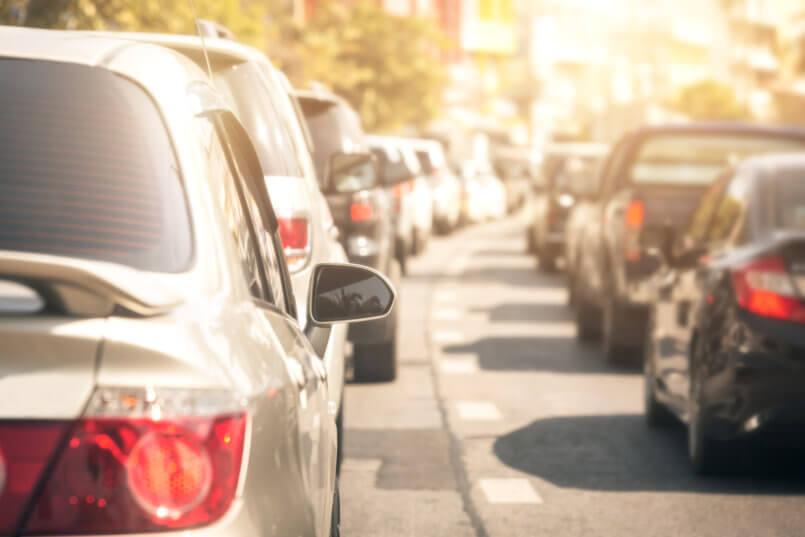 Imagem de carros no trânsito e motoristas pensando em qual bateria comprar
