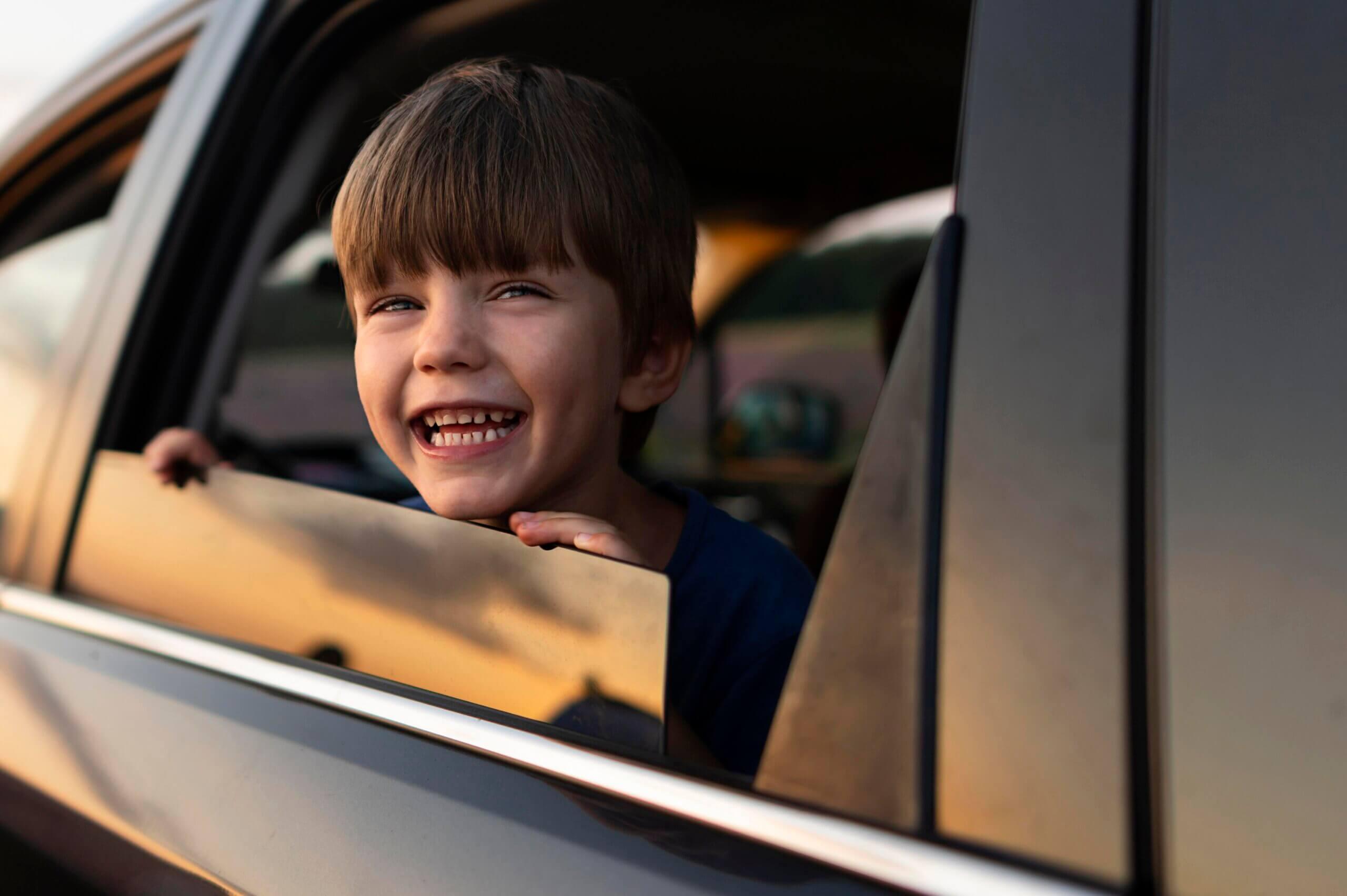 Imagem de um garoto sorrindo através da janela de um carro que possui certificado de garantia Moura