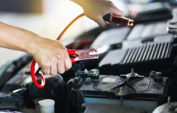 imagem de um cabo sendo usado na bateria automotiva de um carro.
