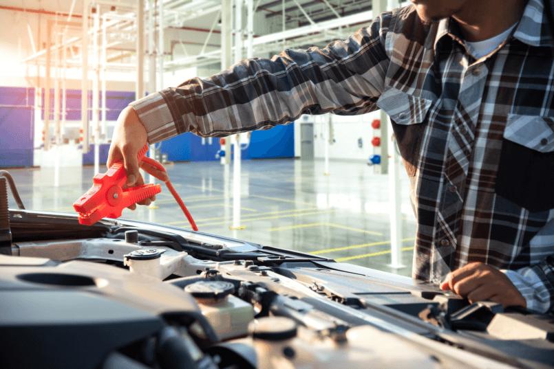 Imagem de homem arrumando o motor em uma loja de bateria de carro.