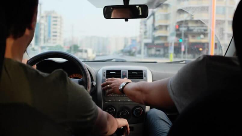 Imagem de duas pessoas em um carro, o motorista está com a mão no câmbio