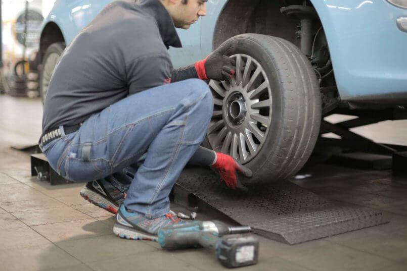 Imagem de um homem trocando pneu de um veículo muito tempo parado