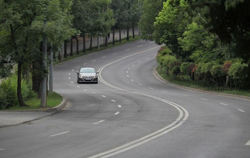 Imagem de carro cinza sozinho em uma estrada
