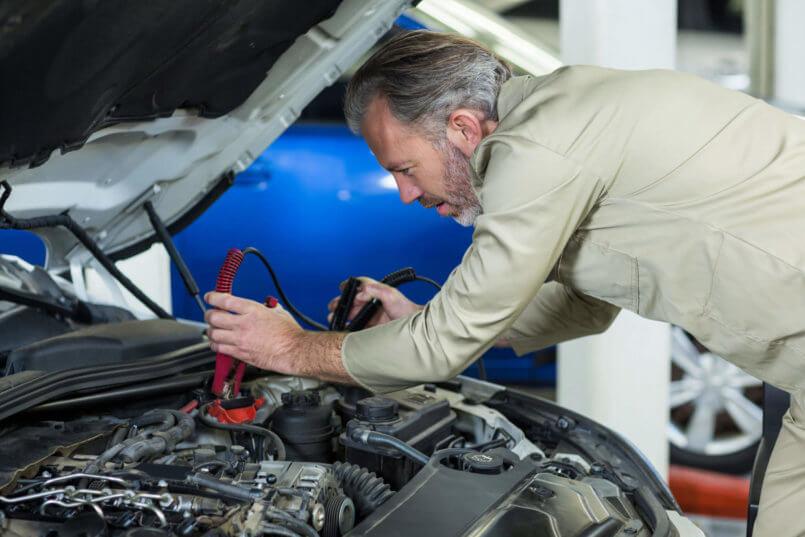 Imagem de um profissional examinando o carro e verificando possíveis causas do significado das luzes do painel
