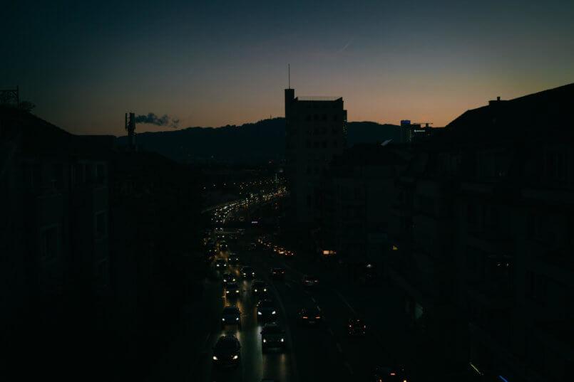 Imagem de faróis de carro a noite, mostrando como carros inteligentes fazem parte do nosso dia a dia