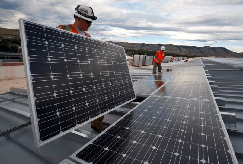 Imagem de um homem segurando um painel sabendo como funciona a energia solar