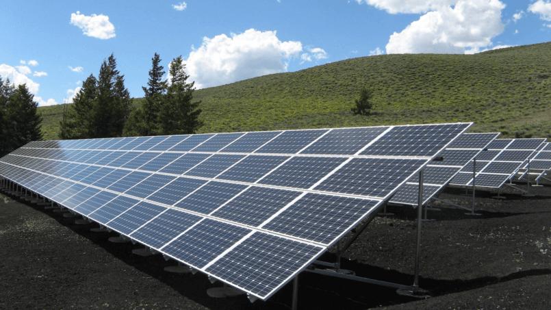 Imagem de painéis na grama para explicar como funciona a energia solar