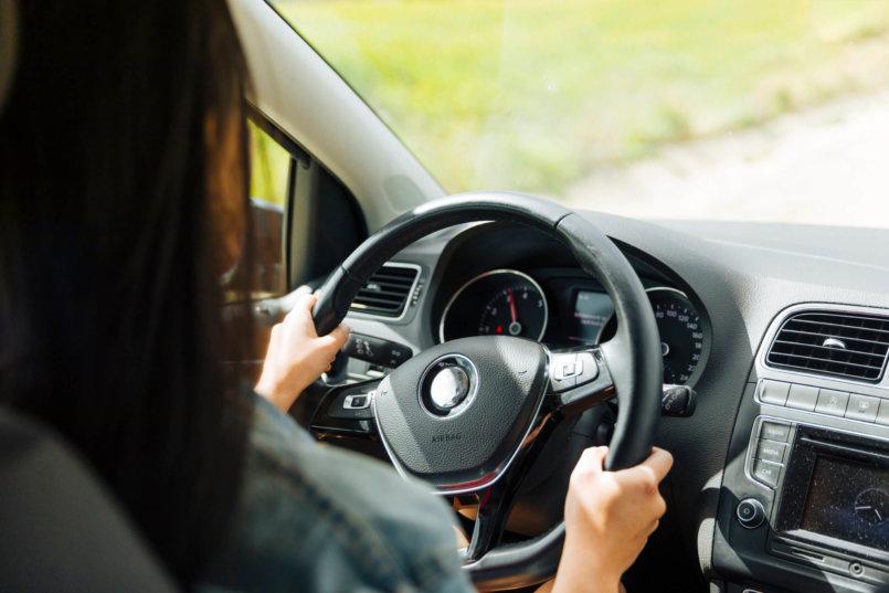 Imagem de uma motorista dirigindo um automóvel com direção hidráulica