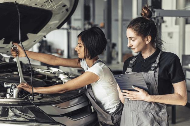 Imagem de duas especialistas checando as dicas automotivas e realizando reparos no veículo