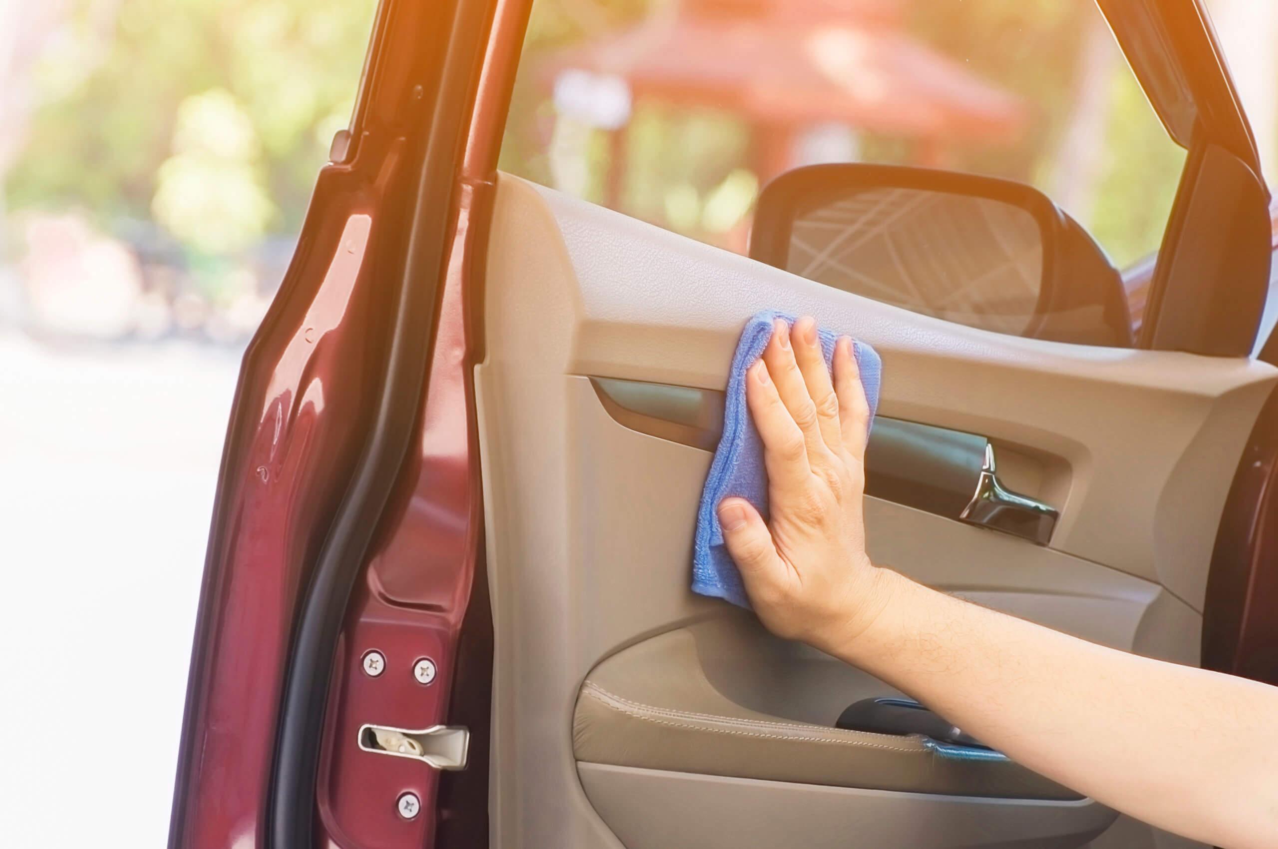 Imagem de uma mão mostrando como higienizar carro adequadamente