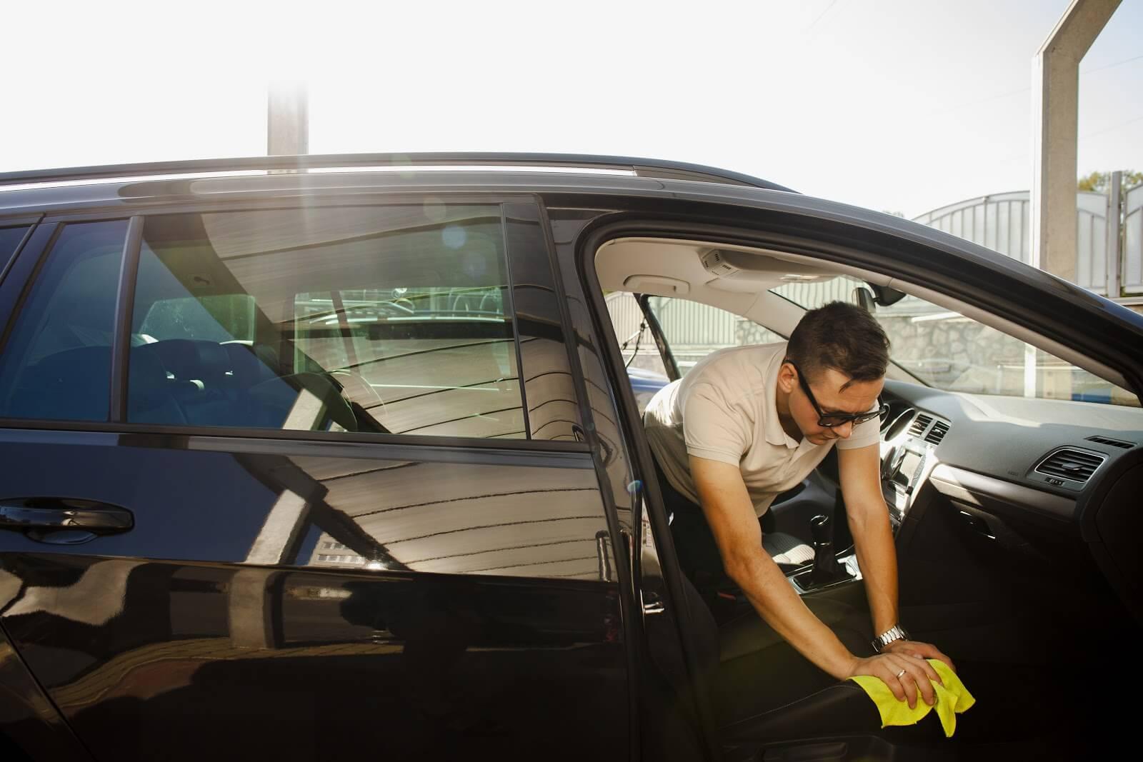 Imagem de um homem limpando o automóvel após sair de carro na quarentena