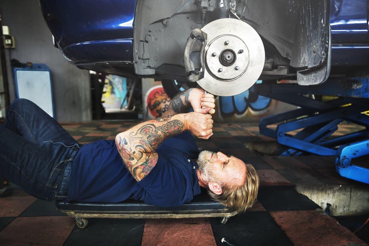Um homem deitado fazendo a troca da pastilha de freio de um carro