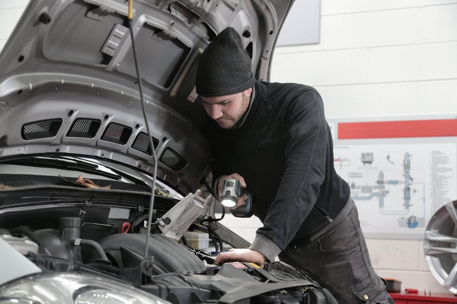 Homem observando a junta do cabeçote de um carro que está com o capô aberto