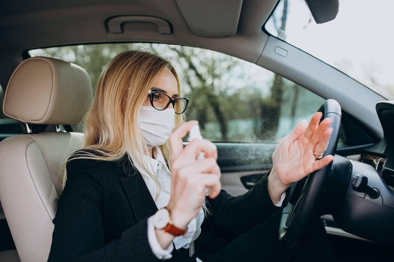Imagem de uma mulher higienizando as mãos após sair de carro na quarentena