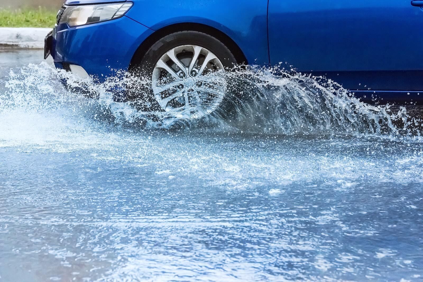 carro azul fazendo aquaplanagem