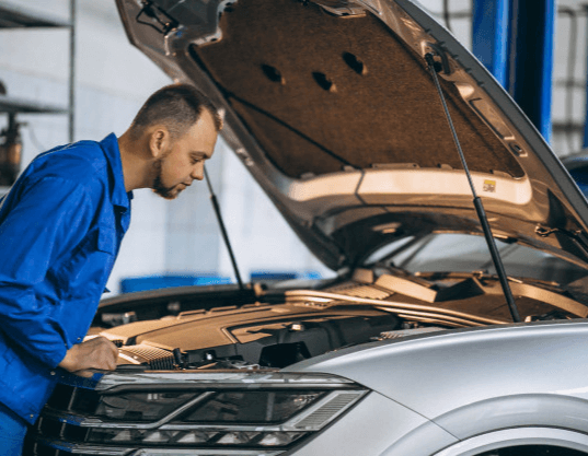 Na imagem, um mecânico está identificando a causa do problema do carro batendo válvula para efetuar o conserto.
