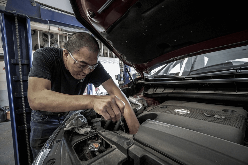 homem fazendo manutenção preventiva no capô de um carro