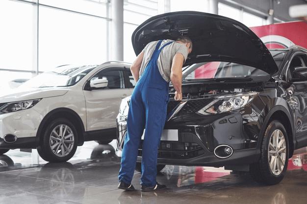homem em pé olhando o capô de um carro para acompanhar o sensor de temperatura