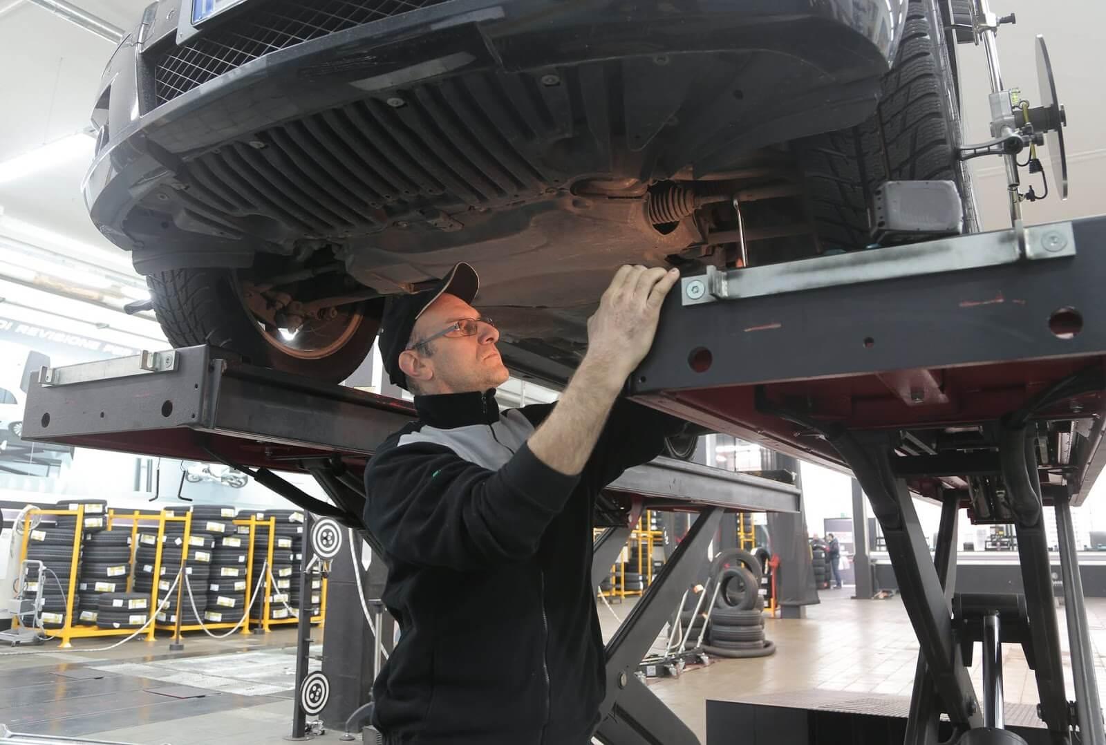 Homem em pé observando a bieleta de um carro