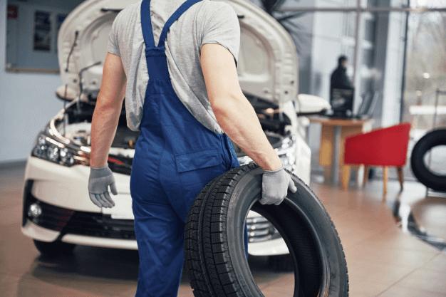 Homem em pé segurando um pneu na frente de um carro fazendo manutenção na junta homocinética