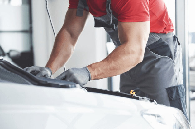 homem fazendo manutenção na válvula EGR de um carro