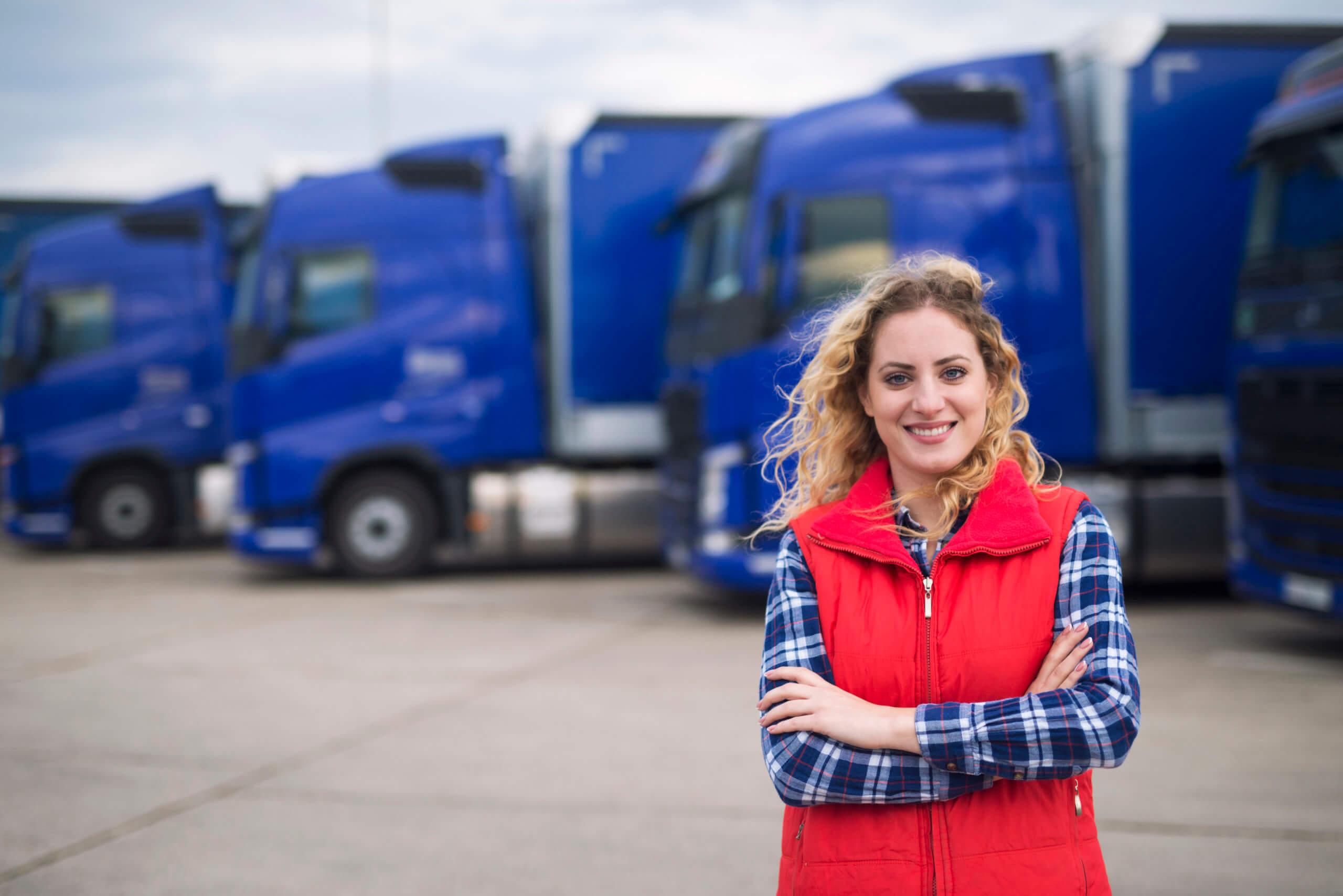 Na imagem, uma caminhoneira está em foco, atrás dela temos vários tipos de caminhões