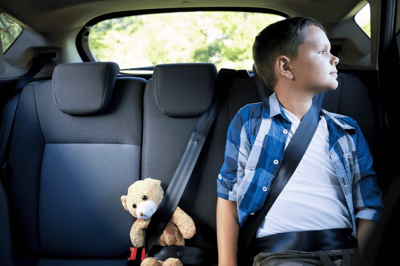 Criança sentada no banco traseiro de um automóvel e ao seu lado um ursinho. Os dois utilizam o cinto de segurança.