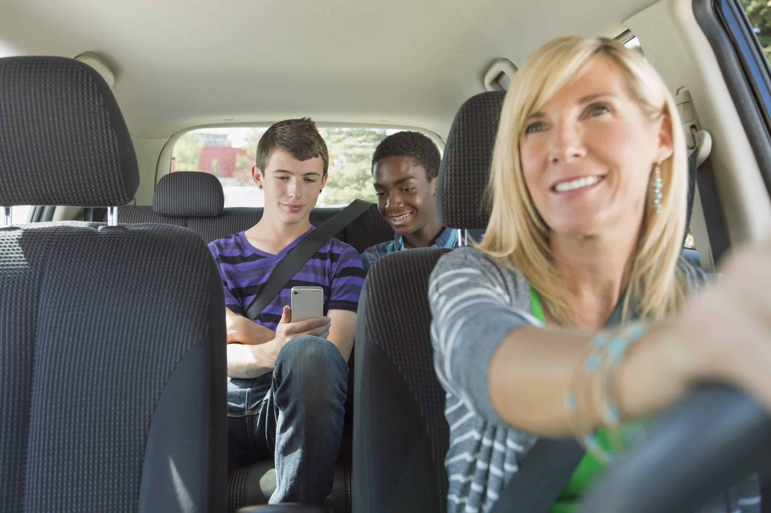 Mulher dirigindo carro, olhando para o banco traseiro pelo retrovisor. Banco traseiro com dois adolescentes olhando para um celular.