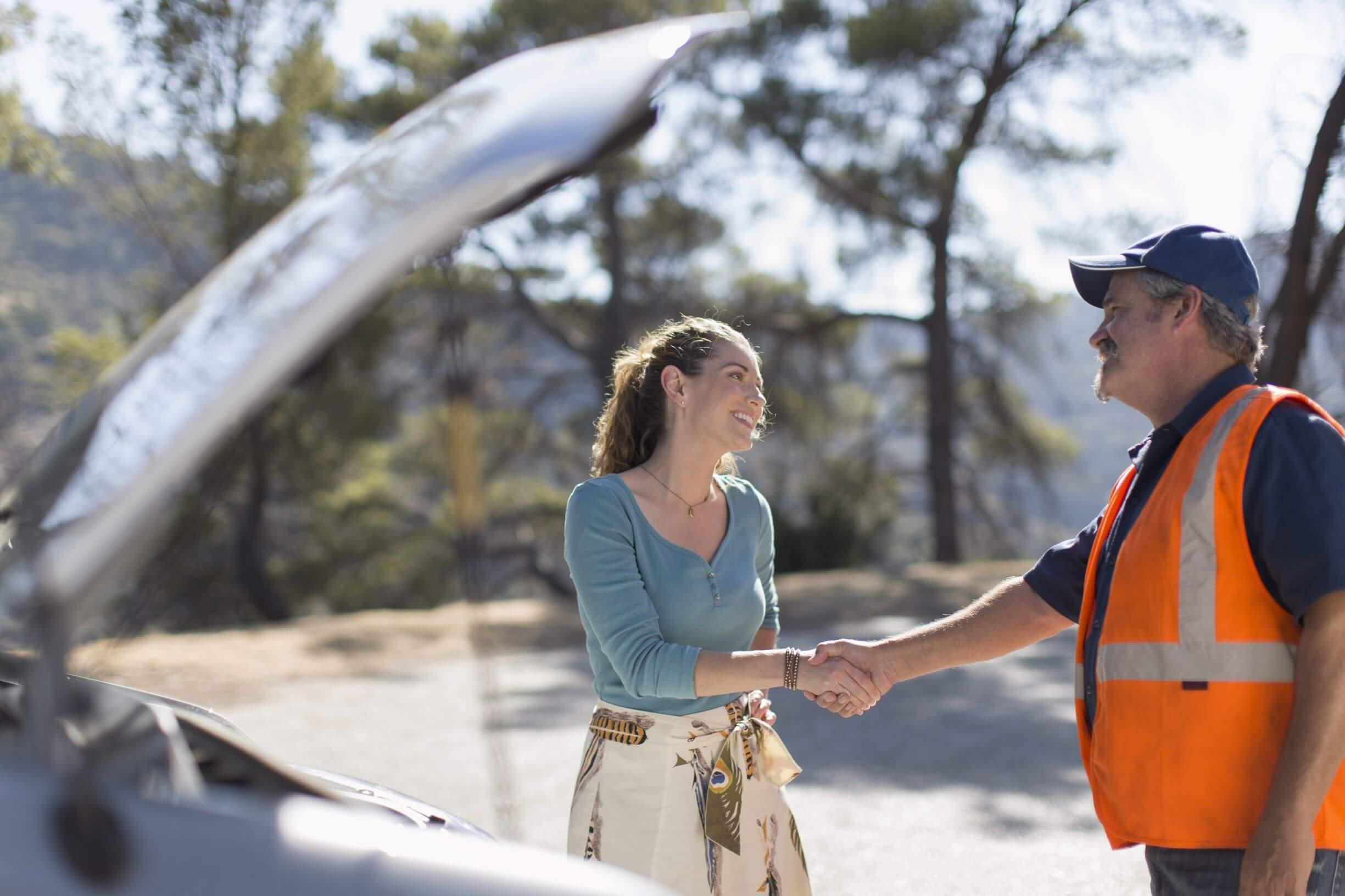 Mulher apertando a mão de homem com colete alaranjado em frente ao seu carro com capô levantado.