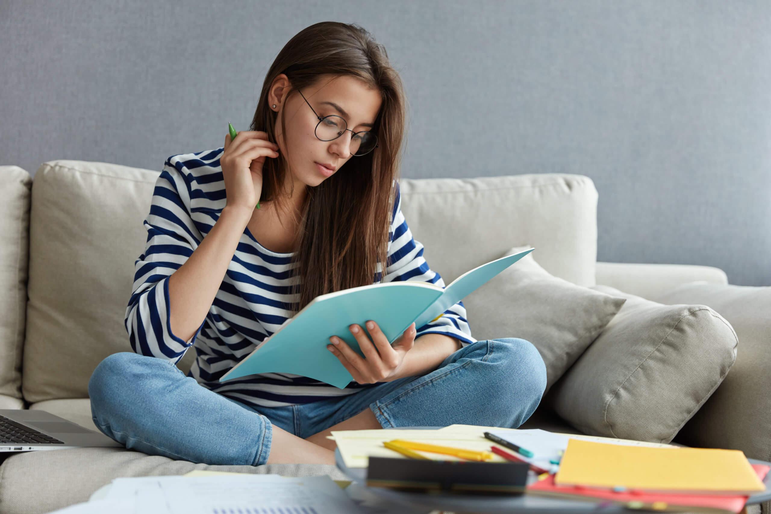 Imagem mostra uma mulher sentada olhando para seus documentos