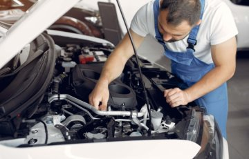 Mecânico de uniforme checando motor de carro