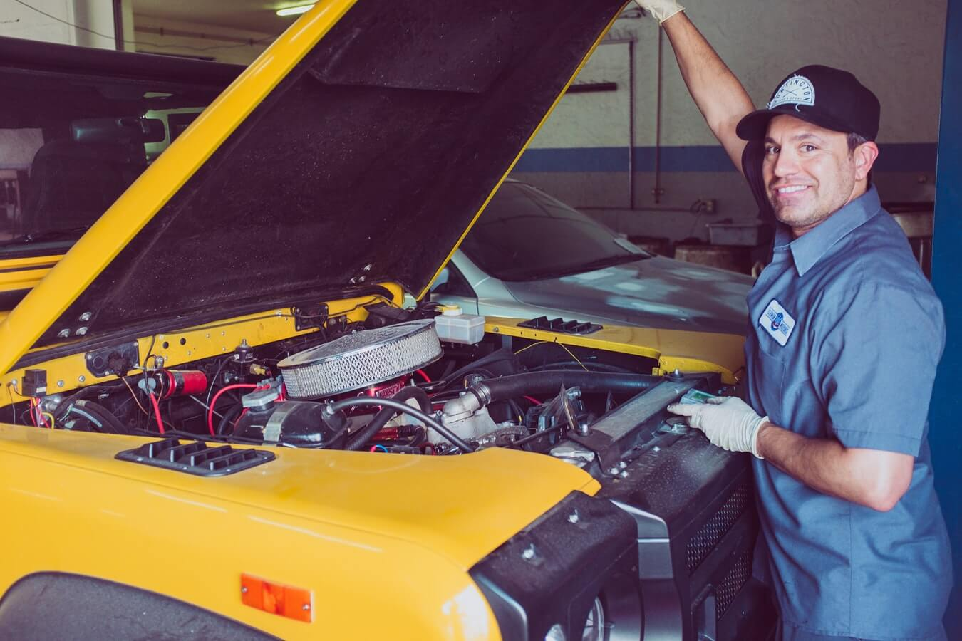 Mecâncio mostrando a parte de dentro de um carro amarelo com capô levantado