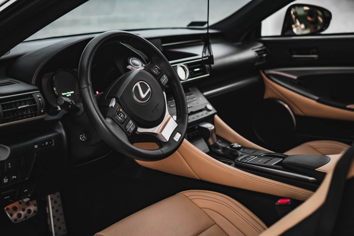 Parte interna de um veículo de luxo, mostrando volante, bancos e câmbio de marcha de carro