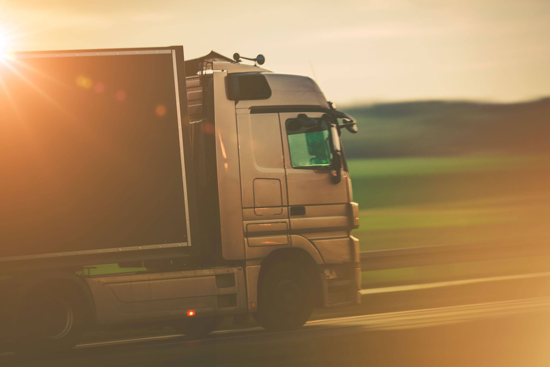 retrato lateral de um caminhão prateado andando passando pela estrada.