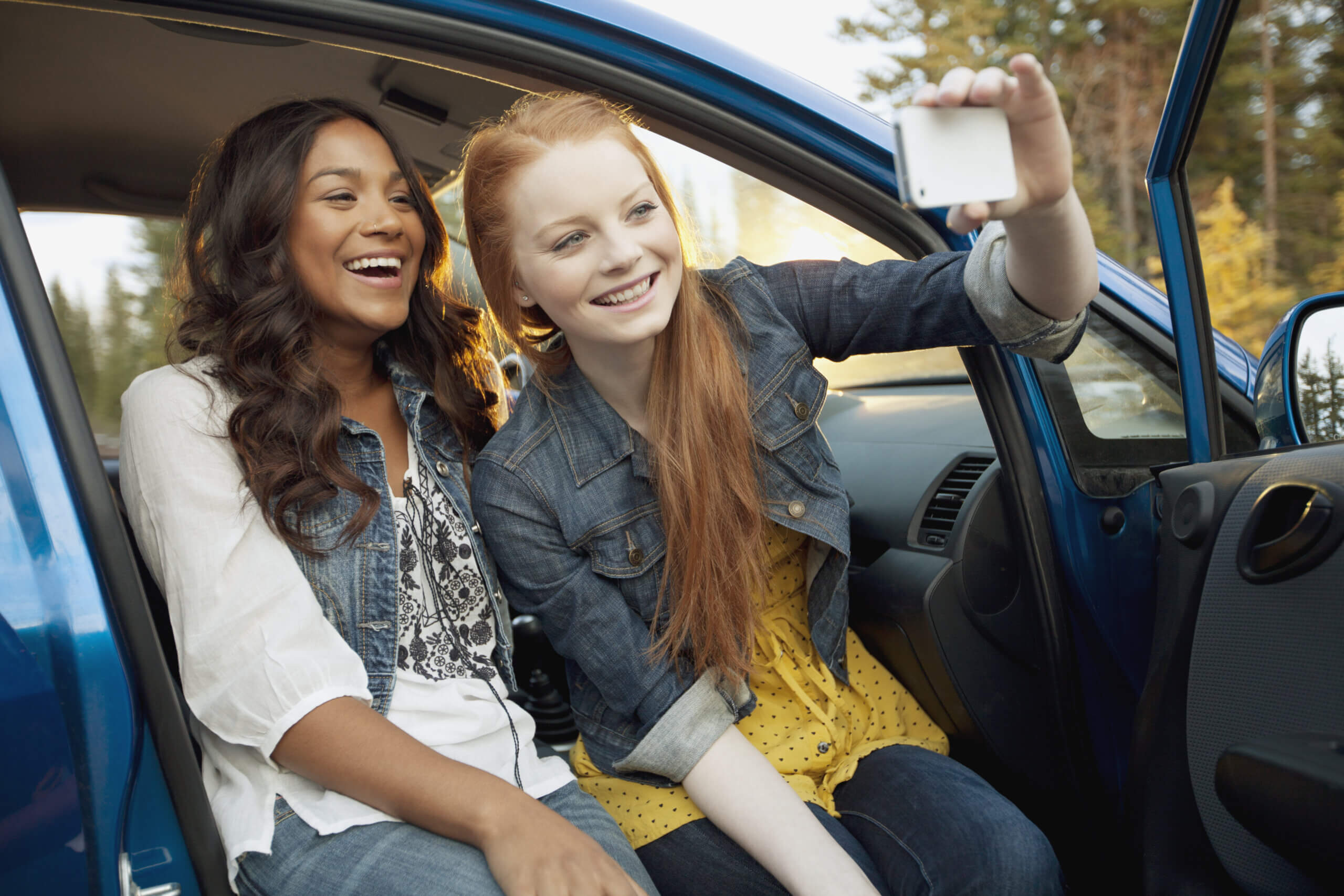 Imagem de um casal de meninas tirando fotos enquanto estão sentadas em um dos tipos de carros para jovens