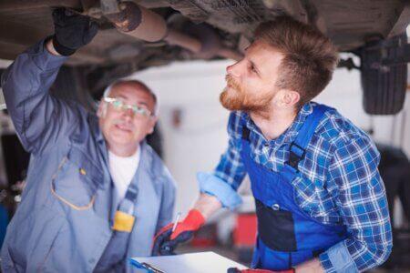 foto de dois mecânicos embaixo de um carro suspenso, verificando algum problema