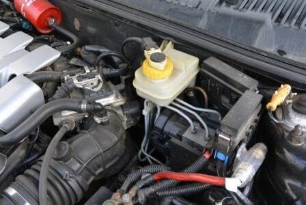 foto de um capô de carro aberto mostrando o compartimento do fluído de freio
