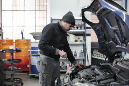 homem de roupa de frio e toca olhando capô do carro aberto