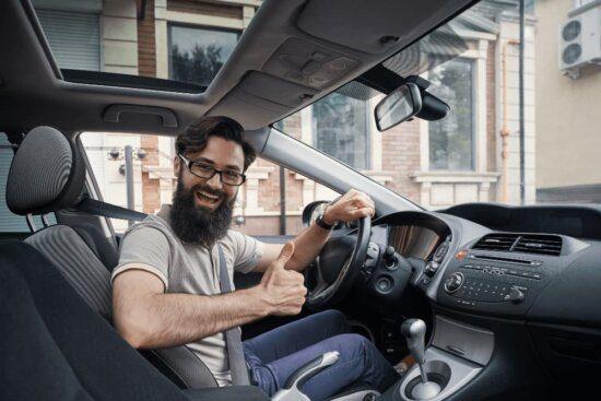 motorista acenando de dentro do carro, feliz.