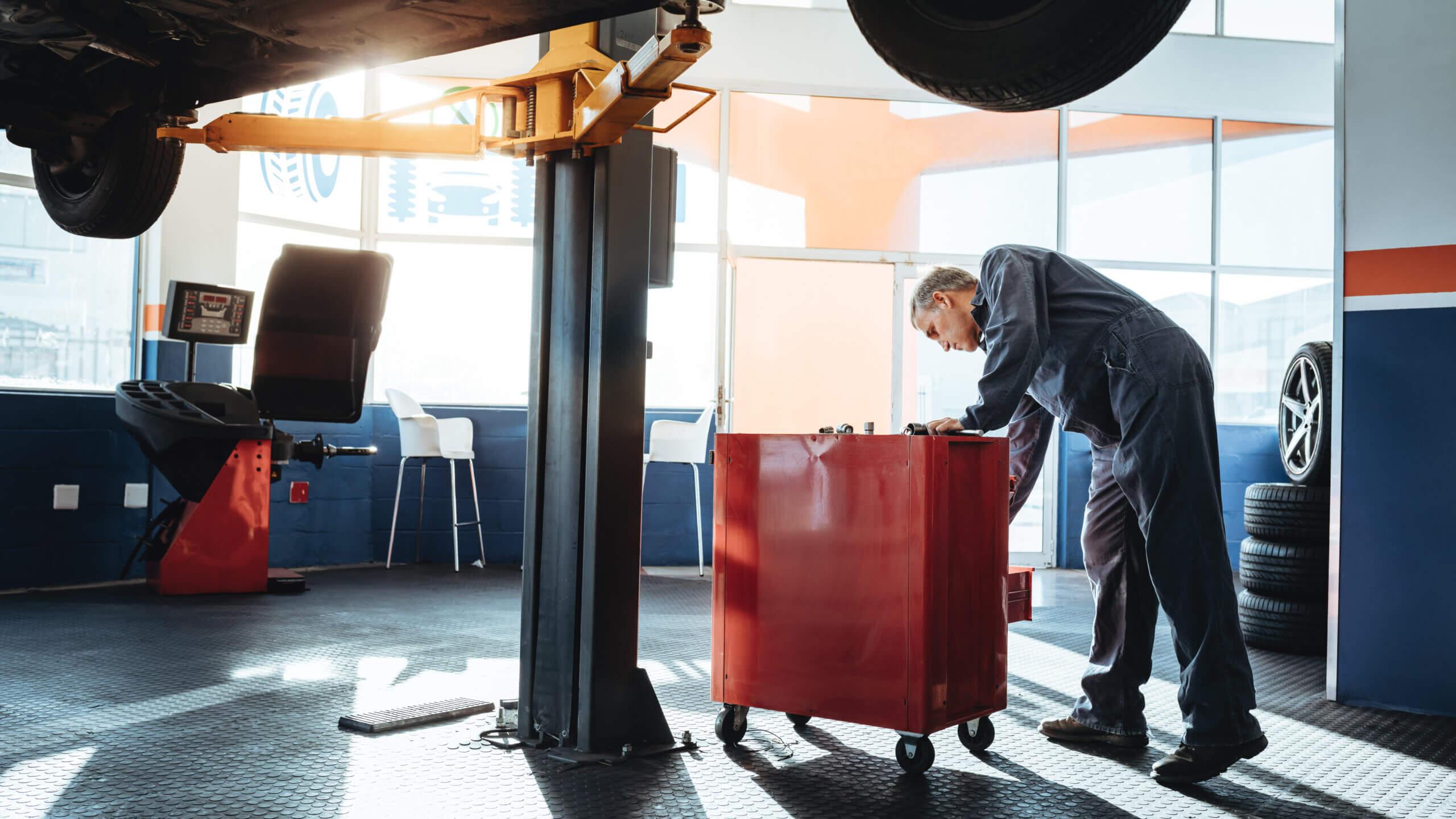 Imagem de oficina mecânica onde se realiza ajustes no balanceamento e alinhamento de veículos.