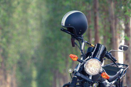 moto estacionada em local arborizado com capacete no guidão