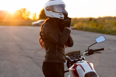 Mulher ao lado de moto estacionada, arrumando seu capacete