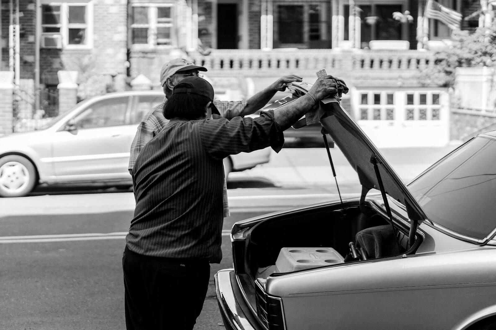 Imagem de duas pessoas verificando um carro que faz barulho quando aumenta a velocidade.