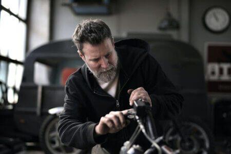 Homem branco com cabelos e barba grisalhos vestindo moletom preto e camiseta branca mexendo com ferramenta para exemplificar problemas na chave codificada