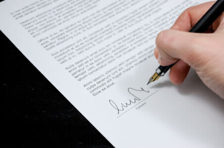Folha de sulfite com contrato sendo assinado por uma pessoa segurando uma caneta para explicar Como obter o Certificado de Segurança Veicular