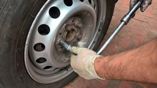Homem branco com luva descartável usando uma ferramenta para desparafusar a calota do pneu mostrando como trocar pneu