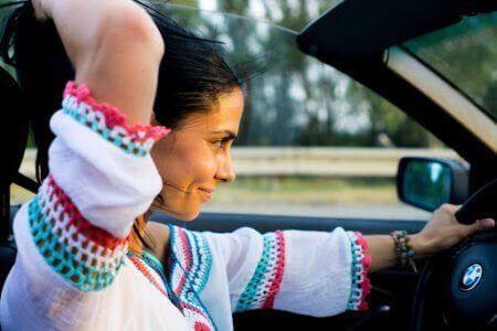 mulher dirigindo carro conversível mexendo no cabelo